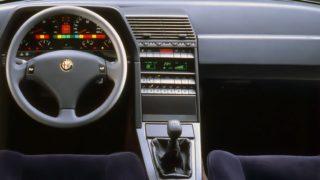 Il posto di guida della Alfa Romeo 164 con volante, tachimetro e la plancia con tutti i comandi.